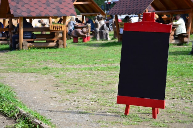 A large board as a menu for an open-air restaurant in a mountainous area.