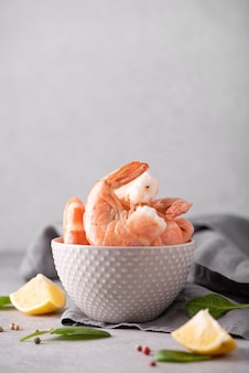 Large boiled shrimp in shell in a gray bowl, close-up