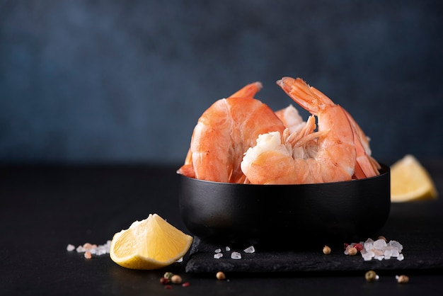 Large boiled shrimp in shell with lemon in a black bowl, close-up