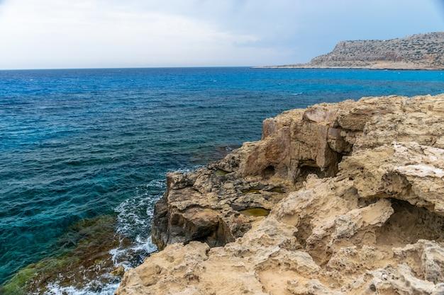 大きな岩が海岸の崖から折れた。 Premium写真