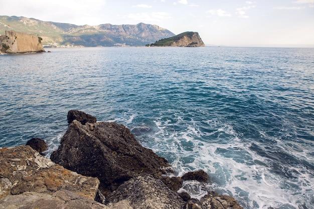 大きな岩が秋にモンテネグロのビーチに横たわっています