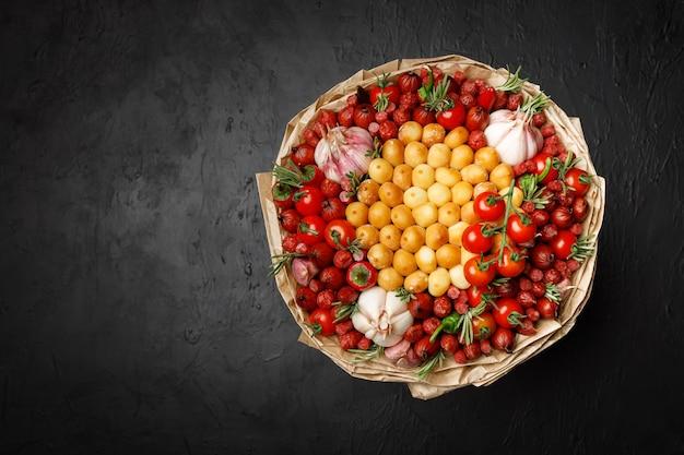 スモークチーズ、ソーセージ、トマト、コショウ、ニンニクをクラフト紙で包んだ大きな花束
