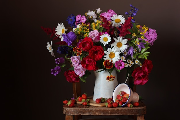 Large bouquet of garden summer flowers in a jug and strawberries on a dark background.