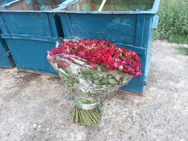 거리에 던져진 빨간 장미의 큰 꽃다발 덤프