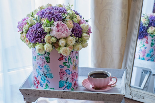 A large bouquet of peonies, roses and hydrangeas in a gift box on a wooden table