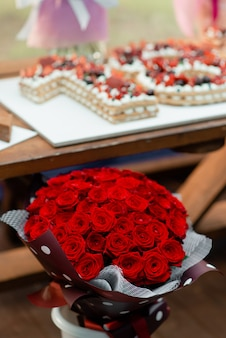 A large bouquet of red roses on the background of a festive cake with a cake.