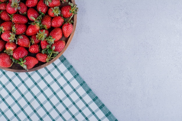 大理石の背景にイチゴでいっぱいの大きなボウル。高品質の写真