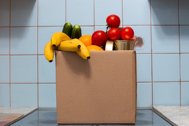 A large box with food and vegetables is in the kitchen, donations for those in need during self-isolation and quarantine