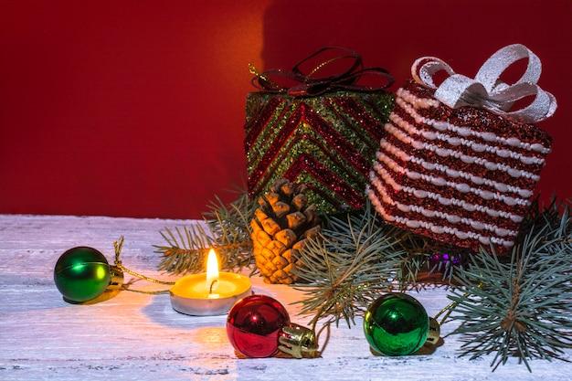 贈り物、カラフルなクリスマスの装飾、トウヒの枝、お祝いの赤と白の背景に燃えるキャンドルが付いた大きな箱。