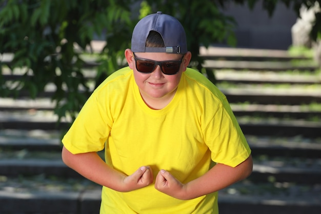 A large boy in a yellow t-shirt tenses his muscle. the concept of body positivity. high quality photo