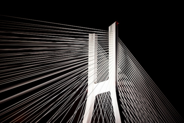 A large bridge with steel cables glows brightly at night