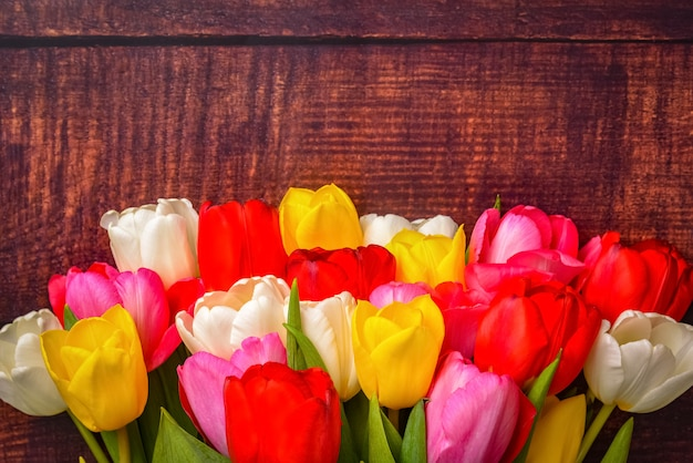 Large bright bouquet of multi-colored tulips on wooden boards of dark brown color.