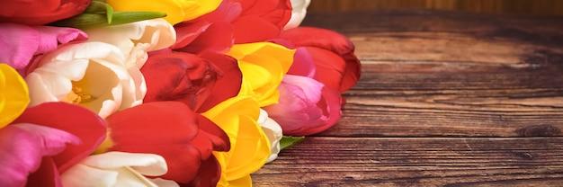 Большой яркий букет из разноцветных тюльпанов на деревянных досках темно-коричневого цвета.