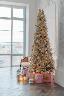 Large bright christmas decor of the living room in vogue style. beautiful, glowing christmas tree.