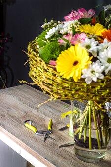 테이블 옆에 있는 작업 꽃집을 위한 크고 창의적인 꽃다발과 도구. 꽃다발 만들기