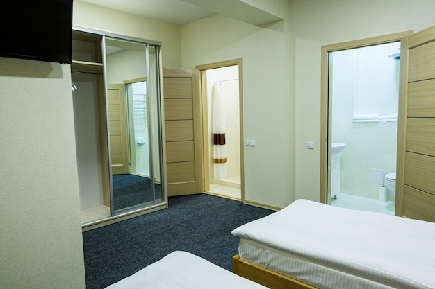 Large bright room in a hostel with three beds. white bedding