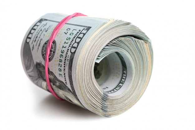 A large bundle of american dollars is stretched with an elastic band.