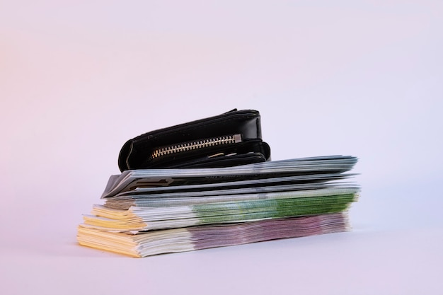 A large bundle of dollars and euros with a wallet on a light background.