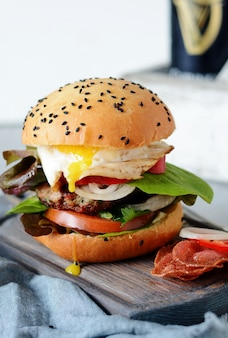 A large burger with a cutlet, vegetables, egg and a fresh roll. sandwich for breakfast. fast food.