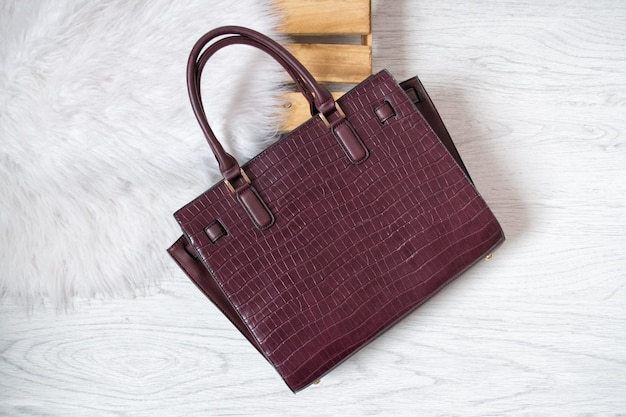 Large burgundy bag on a pallet and white fur. fashionable concept