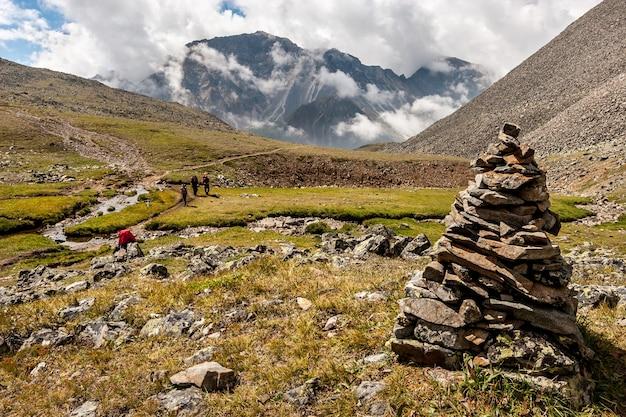 Большая пирамида из камней на переднем плане горного пейзажа с низкими белыми облаками над горами