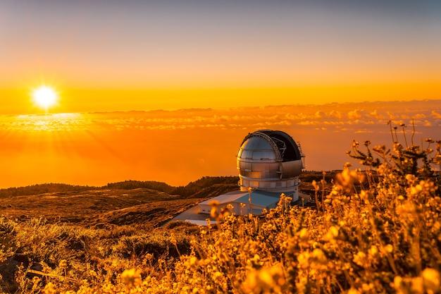 Большой канарский телескоп под названием grantecan optico del roque de los muchachos в кальдере де табуриенте на красивом оранжевом закате, ла пальма, канарские острова. испания