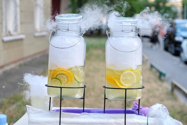 Большие банки натурального лимонада с жидким азотом, сухим льдом. уличные напитки с тобой, пластиковые стаканчики