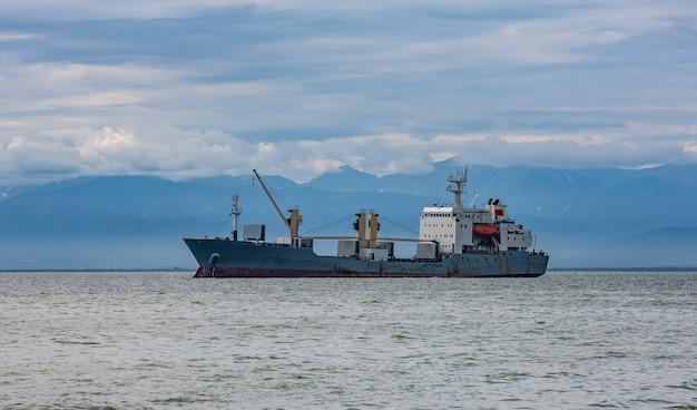Большой грузовой контейнеровоз плывет против вулкана