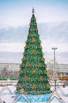 낮, 새해 휴가, 겨울에 도시 광장에 화려한 화환이 있는 대형 크리스마스 트리