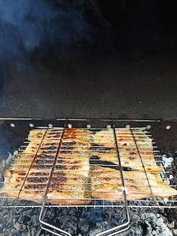 На дровах готовят большие куски красной рыбы, жареный лосось, ароматную здоровую пищу на свежем воздухе.