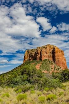 アリゾナ州セドナの雲だらけの青い空の下、木の前に大きな崖