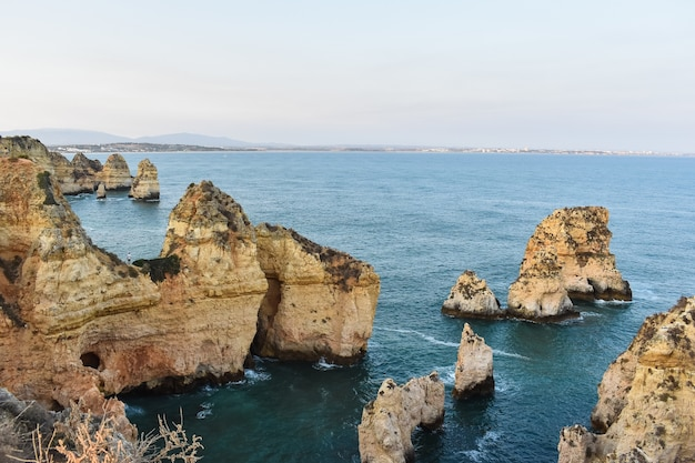 Large cliffs sticking out of the water during daytime in portugal
