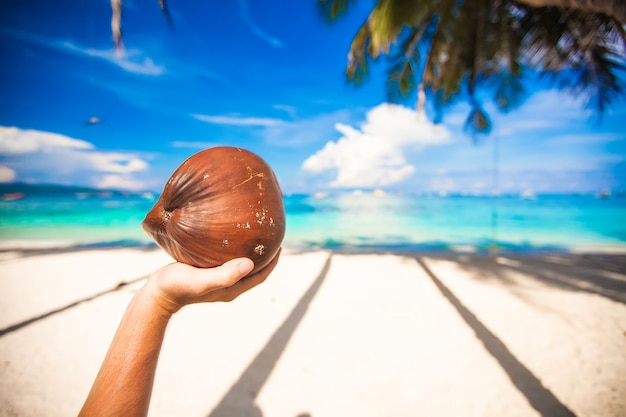 Large coconut in hand turquoise sea and white beach