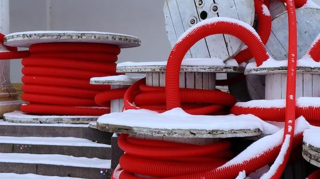 電気設備のケーブルを保護するために使用される赤い柔軟な波形パイプの大きなコイル。配管システムの建設に使用される多くの着色されたポリエチレンプラスチックホース。