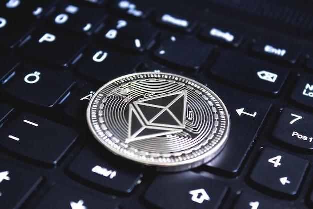 Крупная монета на черной клавиатуре компьютера