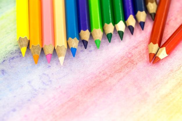 色鉛筆で色付きの背景に大きな色鉛筆のクローズアップ