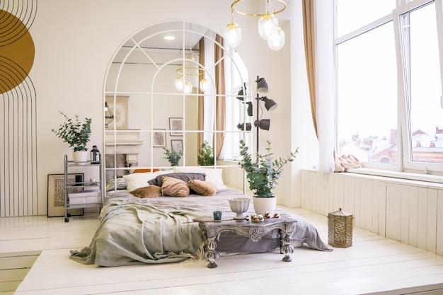 Большая удобная кровать и рабочее место с ноутбуком в стильной квартире. интерьер комнаты. фото высокого качества