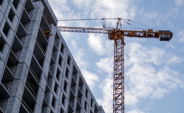 大規模な建設現場。高層住宅団地の資本建設のプロセス。コンクリートの建物、建設、工業用地。空を背景にした産業用クレーン。