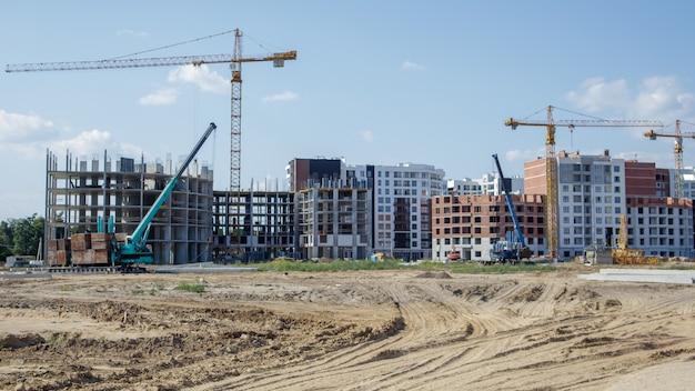 大規模な建設現場。高層住宅団地の資本建設のプロセス。モダンな住宅。コンクリートの建物、建設、工業用地。
