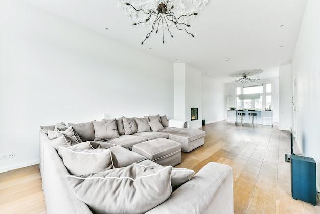 Большой угловой диван с мягкими подушками расположен под элегантной люстрой возле электрокамина в светлой гостиной возле кухни.
