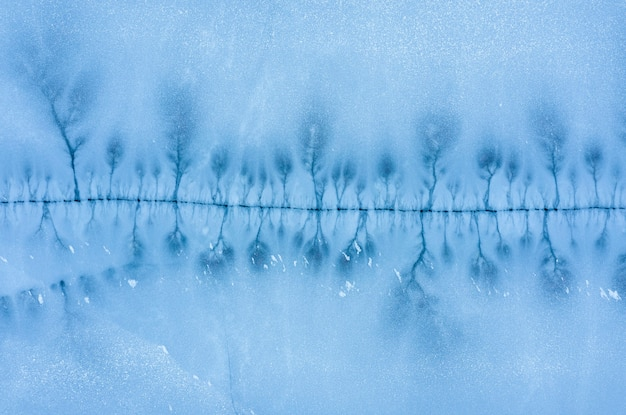 Large crack in the ice surface of a frozen lake. aerial top view.