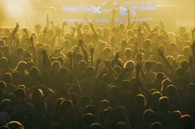 어둠 속에서 경기장 콘서트에서 사람들의 큰 군중
