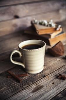 빈티지 나무 바탕에 커피의 큰 컵입니다. 봄 꽃과 책.