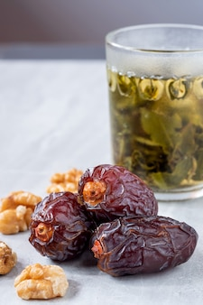 The large date fruits (medjool) with walnut and tea in a glass on a marble floor.
