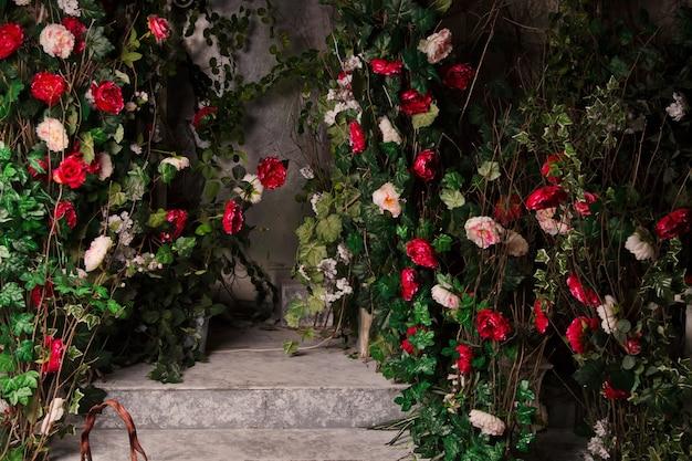 오래된 콘크리트 벽의 배경에 밝은 다색 꽃으로 장식된 큰 덤불