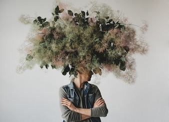 Large decorative bouquet made of green leaves and moss hangs over man's head