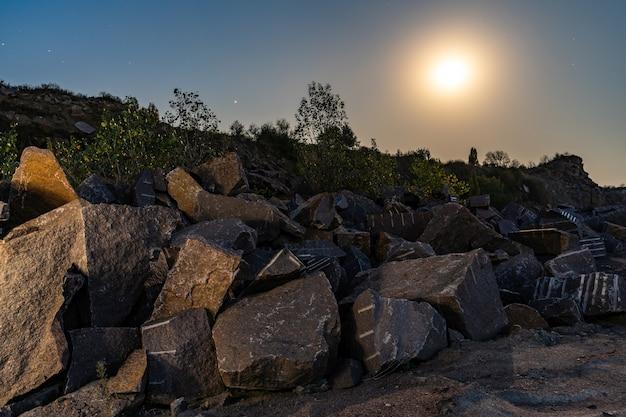 月のある空を背景に、カルパティア山脈の鉱山の近くに大量の石材が堆積している