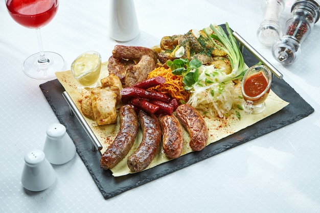 Large dish with grilled sausages, smoked sausages, chicken and pork kebabs with side dishes of baked potatoes and cabbage.