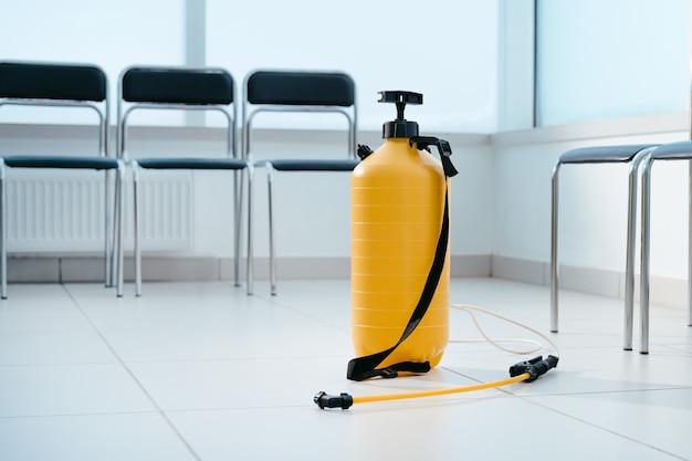 公共レセプションエリアの床にある大型消毒剤噴霧器。コピースペースのある写真。
