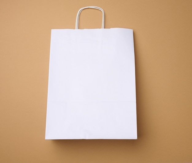 Large disposable white kraft paper bag with handles on a brown background, eco packaging, zero waste